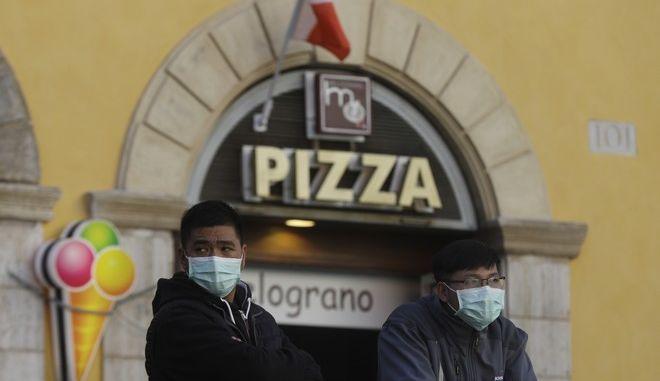 Άνθρωποι φορούν μάσκες προσώπου στη Ρώμη