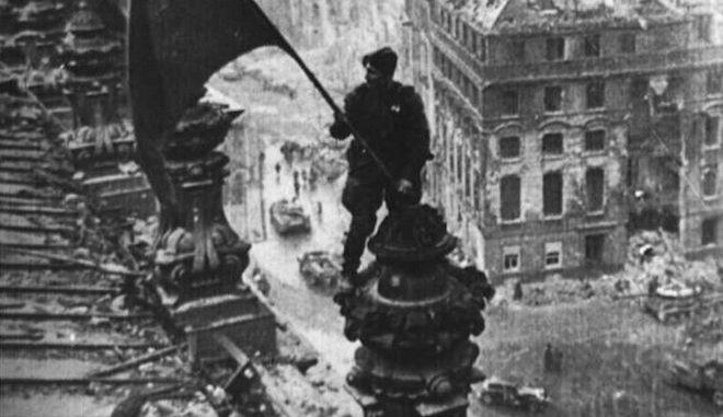 Ένας σοβιετικός στρατιώτης τοποθετεί τη σημαία του έθνους του πάνω από το Ράιχσταγκ, το κτίριο του γερμανικού κοινοβουλίου στο Βερολίνο
