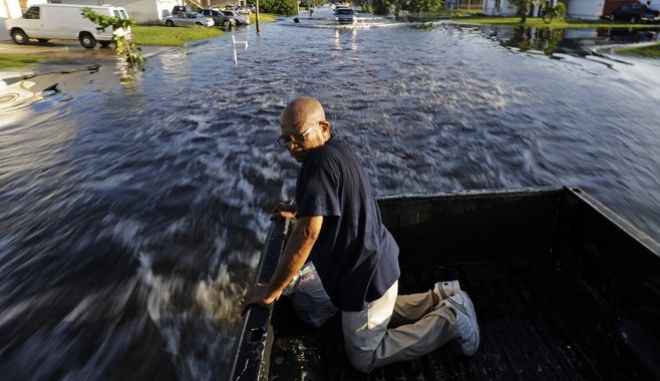 """Jean Chatelier gets a ride from a passing motorist after walking through a flooded street from Hurricane Irma to retrieve his uniform from his house to return to work today at a supermarket in Fort Myers, Fla., Tuesday, Sept. 12, 2017. Chatelier walked about a mile each way in knee-high water as a Publix supermarket was planning on reopening to the public today. """"I want to go back to work. I want to help,"""" said Chatelier. (AP Photo/David Goldman)"""