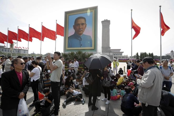 Visitors rest near a portrait of Sun Yat-sen, who is widely regarded as the founding father of modern China, at Tiananmen Square on China's National Day in Beijing, Sunday, Oct. 1, 2017. Hundreds of thousands foreign and domestic tourists flock to the square to celebrate the 68th National Day and the Mid-Autumn Festival over the week-long holidays. (AP Photo/Andy Wong)