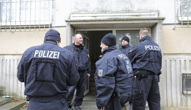 Police stand in front of a building in the northeastern German city of Schwerin Tuesday, Oct. 31, 2017 after German authorities arrested a 19-year-old Syrian citizen there for allegedly planning a bomb attack with high explosives in order to kill a large number of people.  (Bernd Wuestneck/dpa via AP)