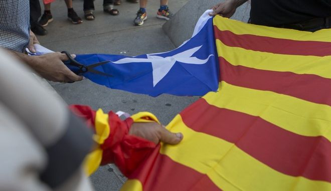 Right wing Falange party supporters cut out the star from 'Estelada', unofficial flag typically flown by Catalan independence supporters, the during a rally in Madrid, Spain, Saturday, Oct. 7, 2017. The demonstrators protested the Catalan regional government's drive to separate from Spain. (AP Photo/Paul White)