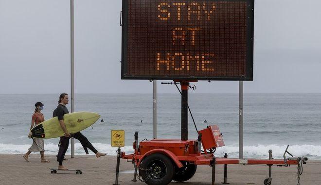 Στιγμιότυπο από την Αυστραλία. Πινακίδα ζητά από τους πολίτες να παραμείνουν στο σπίτι