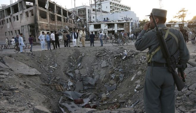 Security forces stand next to a crater created by massive explosion in front of the German Embassy in Kabul, Afghanistan, Wednesday, May 31, 2017. The suicide truck bomb hit a highly secure diplomatic area of Kabul killing scores of people and wounding hundreds more. (AP Photo/Rahmat Gul)
