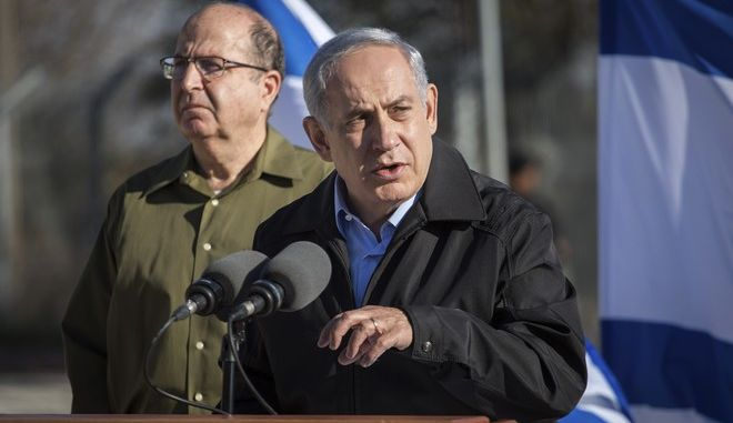 Israel's Prime Minister Benjamin Netanyahu stands with Defense Minister Moshe Yaalon, left,  as he speaks during a visit to an army base near the Gush Etzion bloc of Jewish settlements in the West Bank Monday, Nov. 23, 2015. Netanyahu pledged to keep up Israels tough hand against Palestinians attackers. (Emil Salman/Pool via AP)