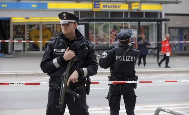 Police officers secure the area after a knife attack at a supermarket in Hamburg, Germany, Friday, July 28, 2017. German police say one person died and several people suffered stab wounds. (Markus Scholz/dpa via AP)