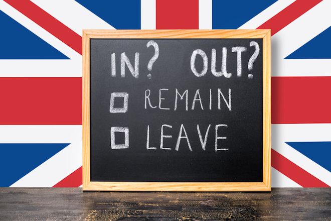 Brexit UK EU referendum concept with flag and handwriting text in, out, leave, remain is written in chalkboard, close up