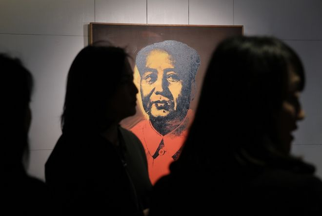 Staff members stand in front of a painting
