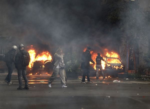 People walk past burning cars as clashes broke out with police during a protest against the Expo 2015 fair in Milan, Italy, Friday, May 1, 2015. The Expo 2015 world's fair opened Friday for a six-month run and its theme is