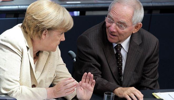 Bundeskanzlerin Angela Merkel (CDU) unterhält sich am Donnerstag (29.09.2011) im Deutschen Bundestag in Berlin mit Bundesfinanzminister Wolfgang Schäuble (CDU). Das Parlament stimmt nach einer Debatte über den Euro-Rettungsschirm ab. Foto: Wolfgang Kumm dpa/lbn