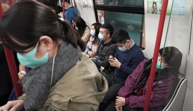 Άνθρωποι στο μετρό της Κίνας, φορούν μάσκες, ύστερα από τα πολλαπλά κρούσματα του κοροναϊού.