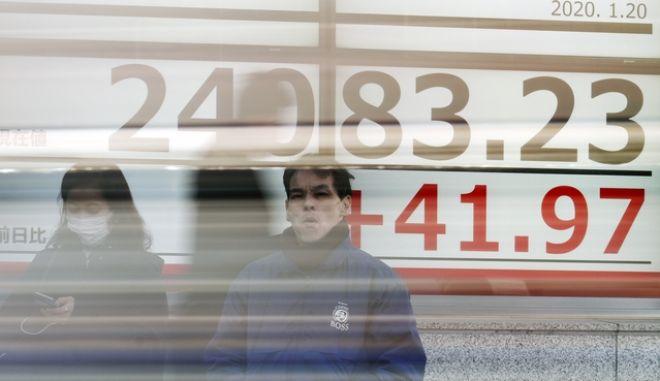 Άνδρας στο Τόκιο στέκεται μπροστά από ηλεκτρονικό πίνακα χρηματιστηρίου