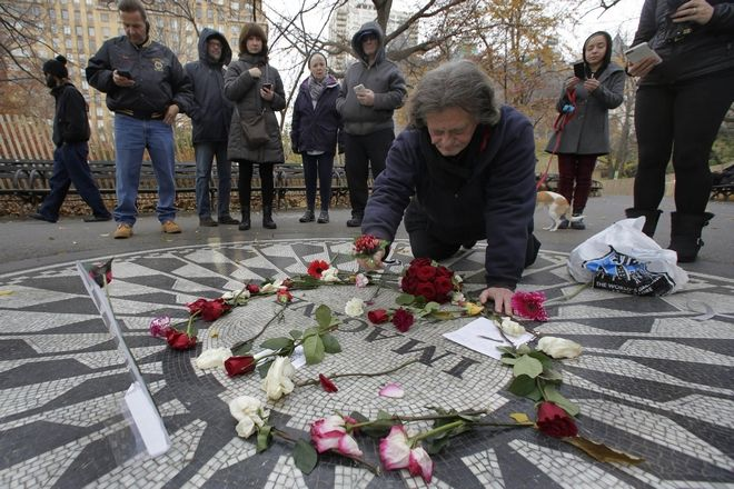Billy Ogansanti arranges flowers on the Imagine mosaic in remembrance of John Lennon, in the Strawberry Fields section of New York's Central Park, Tuesday, Dec. 8, 2015. Thirty-five years ago, Mark David Chapman shot and killed the former the Beatle.  (AP Photo/Richard Drew)