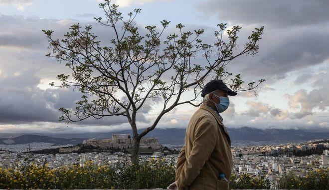 Άνδρας με μάσκα περπατά σε δρόμο με φόντο την Ακρόπολη.