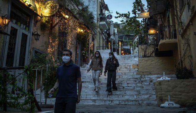 Άνθρωποι που φορούν μάσκα περπατούν στην Πλάκα