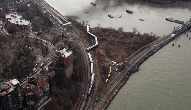 A Metro-North passenger train lays on it's side after derailing in the Bronx borough of New York, Sunday, Dec. 1, 2013. The train derailed on a curved section of track in the Bronx on Sunday morning, coming to rest just inches from the water and causing multiple fatalities and dozens of injuries, authorities said. Metropolitan Transportation Authority police say the train derailed near the Spuyten Duyvil station. (AP Photo/Mark Lennihan)