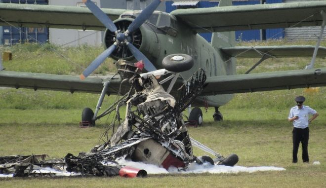 Debris of a crashed plane lies in an airfield at Balashikha, just outside Moscow, in Russia, on Saturday, Sept. 2, 2017. A biplane flying in an airshow just outside the Russian capital has crashed in front of spectators, killing both people aboard. (AP Photo)
