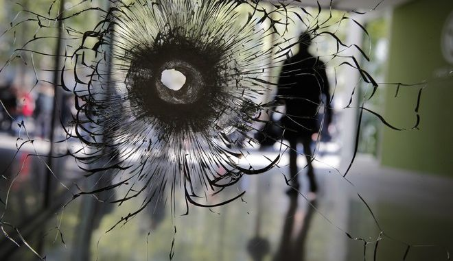 Cracks radiate from a bullet hole in a shopwindow of the Champs Elysees boulevard in Paris, Friday, April 21, 2017. A police officer was killed on the French capital's most famous boulevard when an assailant opened fire with an assault rifle in the name of the Islamic State group. (AP Photo/Christophe Ena)