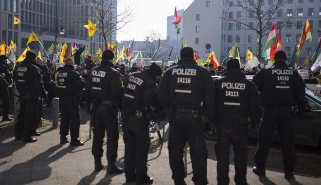 German police officers observe a demonstration of some thousands protestors, against the Turkish offensive targeting Kurds in Afrin, Syria, in Berlin, Germany, Saturday, March 3, 2018. (AP Photo/Markus Schreiber)
