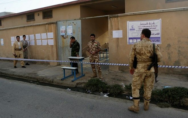 Kurdish security services stand guard outside polling center shortly before opening for the referendum on independence from Iraq in Irbil, Iraq, Monday, Sept. 25, 2017. (AP Photo/Khalid Mohammed)