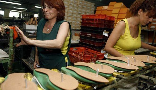 Εργάτριες δουλεύουν σε στιγμιότυπο σε βιοτεχνία υποδημάτων