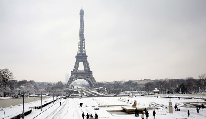 People walk in the Trocadero gardens in front of the Eiffel Tower, in Paris, Wednesday, Feb. 7, 2018. Heavy snowfall has caused major travel disruptions in the northern half of France and in Paris as the weather conditions caught authorities off guard. (AP Photo/Thibault Camus)