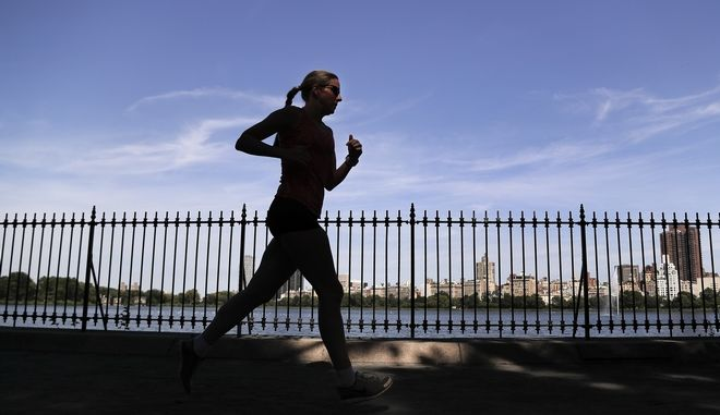 A woman jogs through Central Park, Tuesday, Aug. 9, 2016, in New York. The slayings over the past week of two women who had gone running in New York City and rural Massachusetts just reinforce the fears of many female athletes and help explain why untold numbers avoid working out alone, at night or in secluded places. (AP Photo/Julie Jacobson)