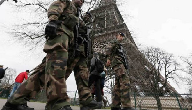 """French soldiers patrol near the Eiffel Tower in Paris as part of the """"Vigipirate"""" security plan December 23, 2014. French security forces stepped up protection of public places on Tuesday after three acts of violence in three days left some 30 wounded and reignited fears about France's vulnerability to attacks by Islamic radicals.  REUTERS/Gonzalo Fuentes (FRANCE - Tags: TRAVEL MILITARY POLITICS)"""