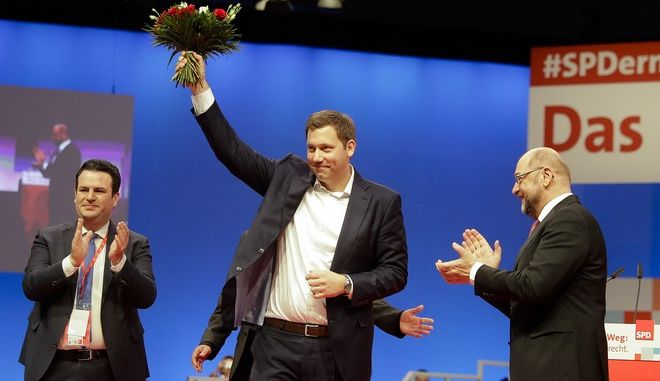 Social Democratic Party, SPD, chairman Martin Schulz, right, and outgoing Secretary General Hubertus Heil, left, applaud to newly elected General Secretary Lars Klingbeil on the second day of the party's convention in Berlin, Friday, Dec. 8, 2017. (AP Photo/Markus Schreiber)