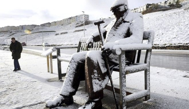 """The Freddie Gilroy sculpture  of a man sitting on a bench is covered in snow at Scarborough northwest England as heavy snowfall is affecting roads across Britain on Tuesday morning after several centimetres fell in some parts overnight. Tuesday Feb. 27, 2018. Police forces have reported """"tricky"""" driving conditions, with forecasters expecting the wintry weather to continue for a few days.  (John Giles/PA via AP)"""