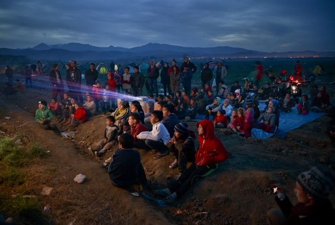 2016 AP YEAR END PHOTOS - Children watch an animated movie in a field at the northern Greek border station of Idomeni on March 5, 2016. The Idomeni border crossing in the Greek region of Central Macedonia has become a bottleneck, where thousands of migrants are trapped as they try to find refuge and a better life in Europe. (AP Photo/Vadim Ghirda, File)
