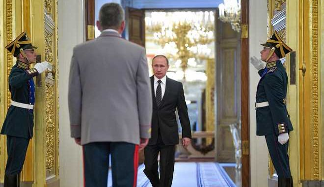 Russian President Vladimir Putin, center background, enters a hall in the Kremlin for a meeting with graduates of military and police academies in Moscow, Russia, Wednesday, June 28, 2017.  Putin has pledged to continue efforts to beef up the Russian military and law-enforcement agencies. (Alexei Druzhinin/Sputnik, Kremlin Pool Photo via AP)
