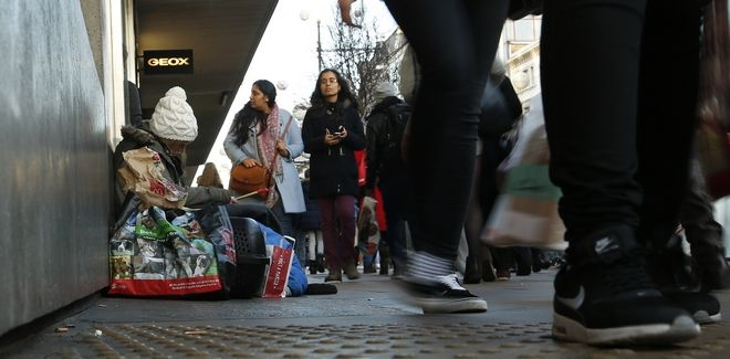 Last minute Christmas shoppers clutching large bags walk a young woman who holds a tin whistle on the pavement outside a department store in London's Oxford Street, Thursday, Dec. 24, 2015. According to recent figures around 4-8,000 people are said to homeless each night in England, according to a recent report by a homeless charity Crisis. (AP Photo/Alastair Grant)