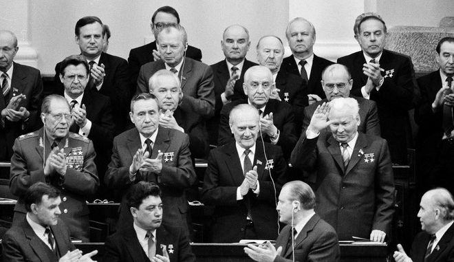 Konstantin Chernenko, right, waves as fellow Politburo members, Foreign Minister Andrei Gromyko, left, and Premier Nikolai Tikhonov, center, and other unidentified members applaud him in Moscow after the Soviet Parliament elected him president, April 11, 1984.  (AP Photo/Boris Yurchenko)