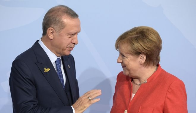 Turkish President Recep Tayyip Erdogan, left, talks to German Chancellor Angela Merkel when arriving on the first day of the G-20 summit in Hamburg, northern Germany, Friday, July 7, 2017. The leaders of the group of 20 meet July 7 and 8. (AP Photo/Jens Meyer)