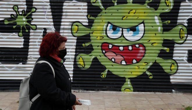 Γυναίκα με μάσκα σε δρόμο της Αθήνας μπροστά από graffiti (Open/Esem).