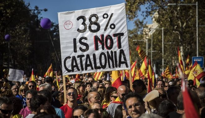 Nationalist activists hold up a banner during a mass rally against Catalonia's declaration of independence, in Barcelona, Spain, Sunday, Oct. 29, 2017. Thousands of opponents of independence for Catalonia held the rally on one of the city's main avenues after one of the country's most tumultuous days in decades. (AP Photo/Santi Palacios)