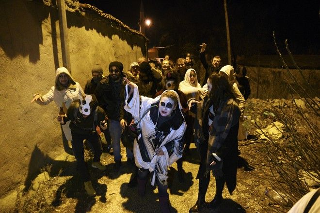 Festival goers with painted faces and wearing costumes to spook locals on what's called