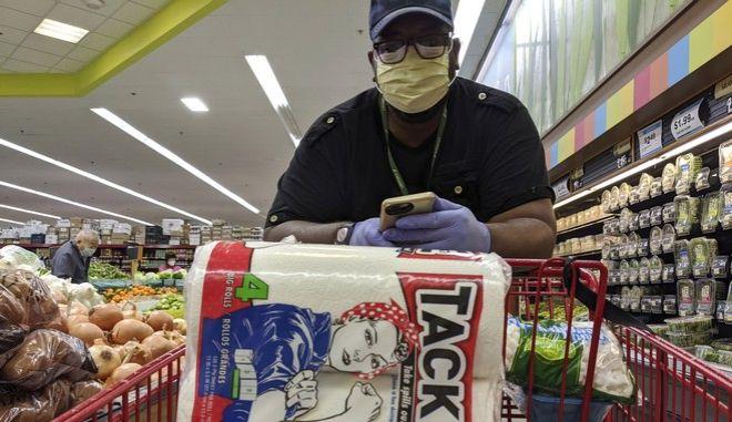 Καταναλωτής σε σούπερ μάρκετ αγοράζει χαρτί υγείας