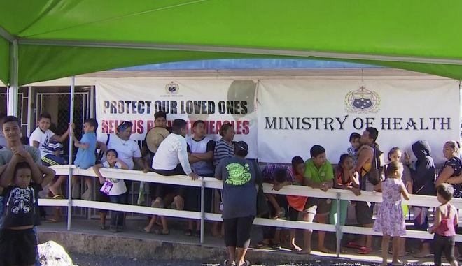 Παιδιά με τους γονείς τους περιμένουν στην ουρά για να εμβολιαστούν.