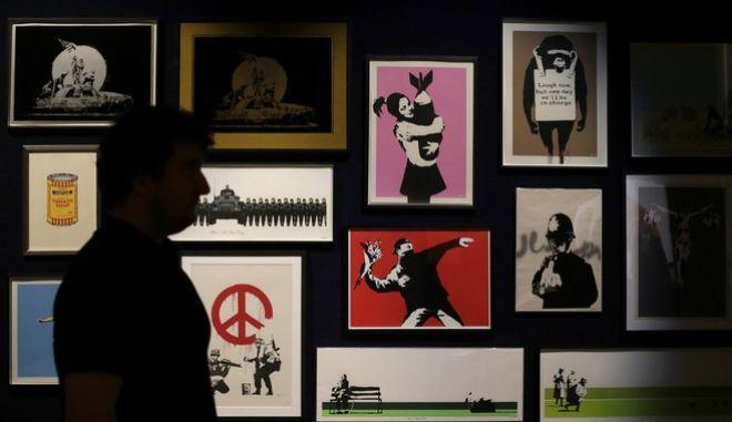 """Αντίγραφα των έργων του Banksy σε δημοπρασία στο Λονδίνο. Στη μέση φαίνεται ο """"μασκοφόρος με το μπουκέτο"""""""