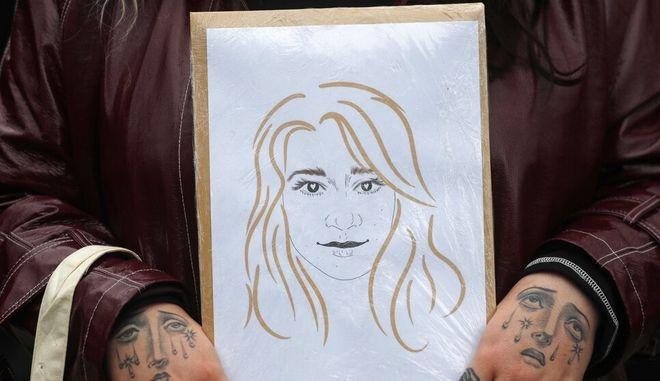 Διαδηλωτής κρατάει στα χέρια του σκίτσο με τη δολοφονημένη Σάρα Έβεραρντ