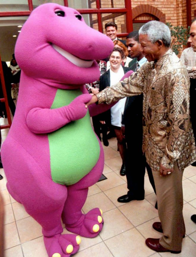 Barney, the purple dinosaur known by children around the world, is greeted by the South African President Nelson Mandela in Johannesburg Monday, March 24, 1997 on the occasion of Barney's first visit to Africa. A donation was made in Barney's name to the Nelson Mandela Children's Fund. (AP Photo)