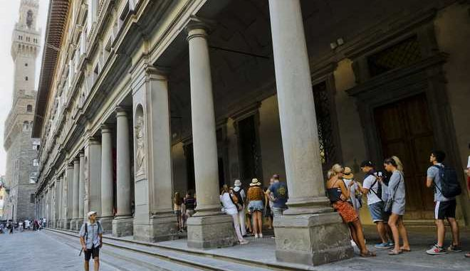 """People line up to enter in the Uffizi Gallery in Florence, Italy, Tuesday, Aug. 1, 2017. The famed Uffizi Gallery in Florence is taking a swipe at so-called """"hit-and-run tourism,"""" announcing on Monday price increases on single-entry tickets, while inaugurating three-day and annual passes that offer discounted entry with priority access. At left Palazzo Vecchio. (AP Photo/Domenico Stinellis)"""