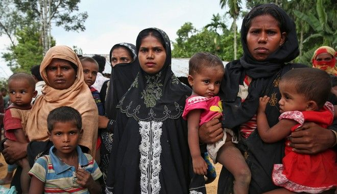 Members of Myanmar's Muslim Rohingya ethnic minority wait to enter the Kutupalong makeshift refugee camp in Cox's Bazar, Bangladesh, Monday, Aug. 28, 2017. Violence in Myanmar's western Rakhine state has driven thousands of ethnic Rohingya Muslims fleeing toward Bangladesh for safety, along with a smaller exodus of ethnic Rakhine Buddhists. (AP Photo/Mushfiqul Alam)