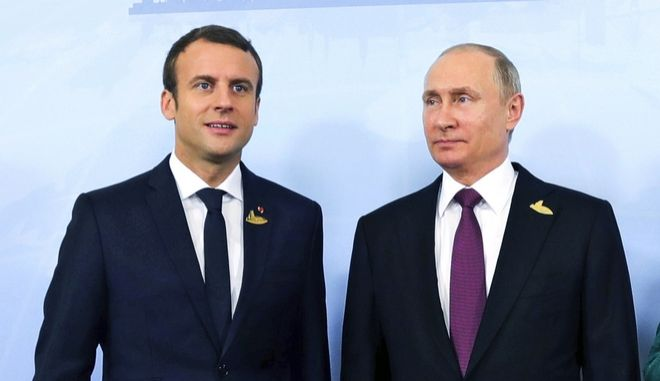 German Chancellor Angela Merkel, right, poses with French President Emmanuel Macron, left, and Russia's President Vladimir Putin prior to a meeting during the G20 summit in Hamburg, Germany, Saturday, July 8, 2017. Leaders of the world's top economic powers are wrapping up their search for common ground on trade, climate change and a host of other issues at the Group of 20 summit in Hamburg Saturday, a meeting overshadowed by violent clashes between anti-globalization activists and police. (Mikhail Klimentyev, Kremlin Pool Photo via AP)