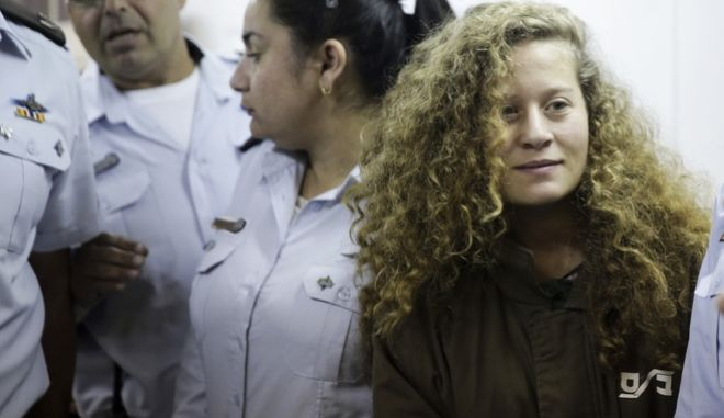 "FILE - In this Dec. 28, 2017 file photo, Ahed Tamimi is brought to a courtroom inside Ofer military prison near Jerusalem. A senior Israeli official on Wednesday said he led a secret investigation into 16-year-old Palestinian protest icon Ahed Tamimi and her family, in part because their appearance, including ""blond-haired, freckled"" children in Western clothes, made them seem less like real Palestinians. (AP Photo/Mahmoud Illean, File)"