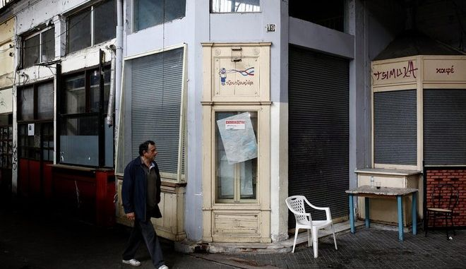 A man walks past a closed store at Modiano covered market in Thessaloniki, Greece, on Monday, May 11, 2015.