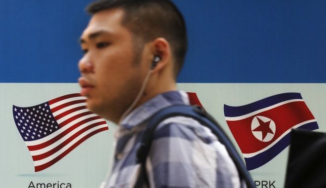 A man walks past a board displaying United States and North Korea national flags in Beijing, Tuesday, May 2, 2017. President Donald Trump opened the door Monday to a future meeting with North Korea's Kim Jong Un, offering unusual praise for the globally ostracized leader at a time of surging nuclear tensions. (AP Photo/Andy Wong)