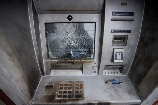 Οι δράστες έσπασαν με βαριοπούλες τον υαλοπίνακα της τράπεζας και την οθόνη του ΑΤΜ
